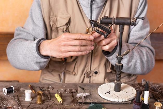 L'uomo che fa la trota vola. attrezzatura per la pesca a mosca e materiale per la preparazione alla pesca a mosca.