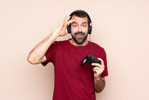 L'uomo che gioca con un controller per videogiochi su un muro isolato ha appena realizzato qualcosa e ha intenzione di risolverlo