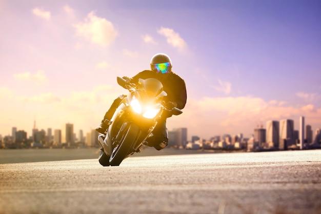 L'uomo che guida il motociclo di sport si appoggia la strada della curva contro l'orizzonte urbano