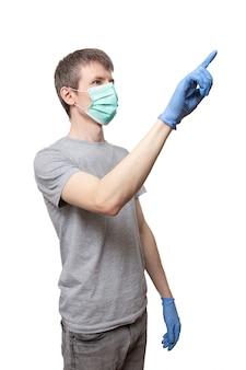 L'uomo che indossa guanti blu, maschera protettiva della medicina indica con il dito