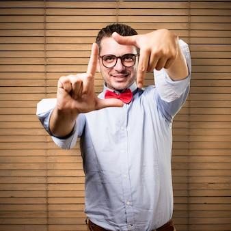 L'uomo che indossa una cravatta a farfalla rossa. facendo una cornice con le sue mani.