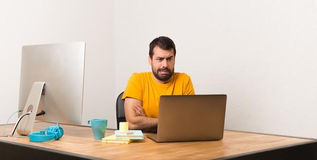 L'uomo che lavora con il laptot in un ufficio è un po 'nervoso e spaventato mentre preme i denti