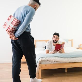 L'uomo che nasconde il presente forma il suo ragazzo che legge il libro