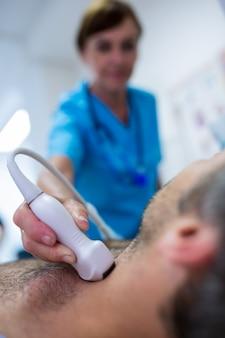L'uomo che ottiene ultrasuono di una tiroide da medico