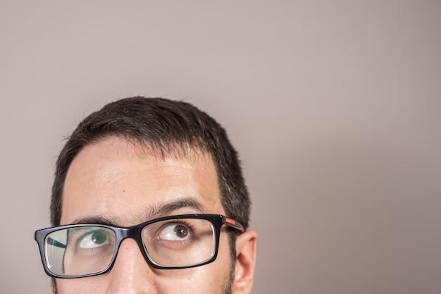 L'uomo che pensa dubbioso, cerca una soluzione che alzi lo sguardo. espressione del volto umano