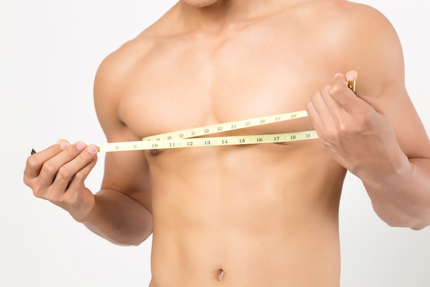 L'uomo che prende le misure del suo corpo. studio sparato su priorità bassa bianca