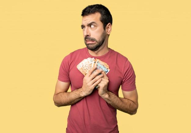 L'uomo che prende un sacco di soldi è un po 'nervoso e spaventato premendo i denti