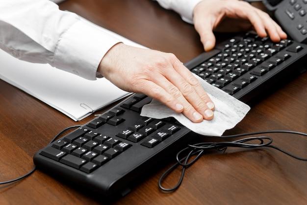 L'uomo che pulisce il posto di lavoro utilizza tovaglioli di carta