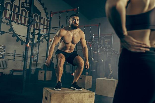 L'uomo che salta durante gli esercizi in palestra. crossfit.