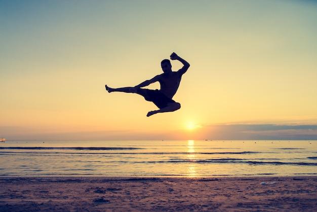L'uomo che salta in un movimento taekwondo sulla spiaggia