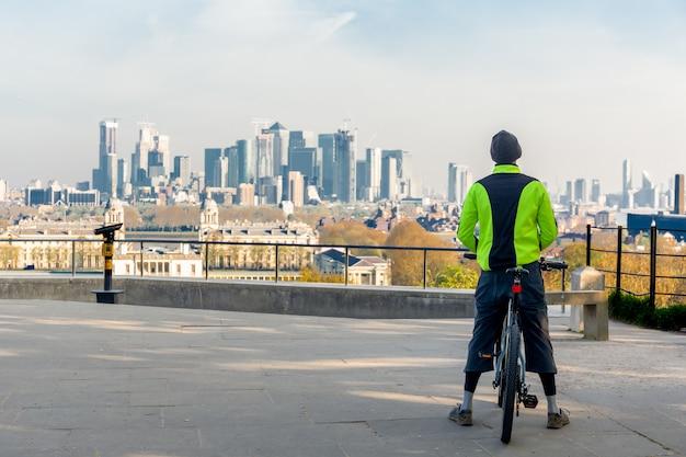 L'uomo che sta sulla bicicletta esamina la vista della città di mattina.