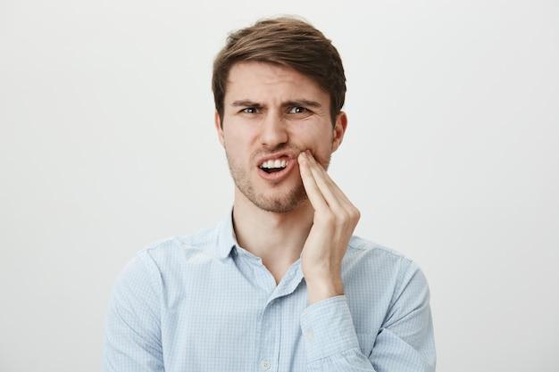 L'uomo che tocca la guancia e fa smorfie dal dolore per il mal di denti, ha bisogno di un dentista