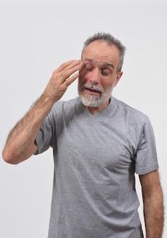 L'uomo con dolore agli occhi su sfondo bianco