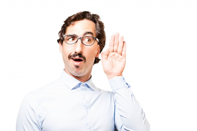 L'uomo con gli occhiali con una mano vicino all'orecchio