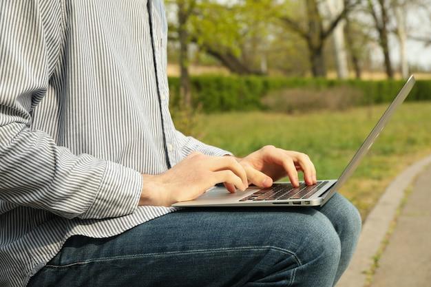 L'uomo con il computer portatile lavora nel parco. lavoro all'aperto