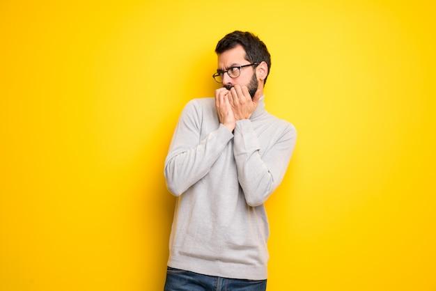L'uomo con la barba e il collo alto è un po 'nervoso e spaventato, mettendo le mani in bocca