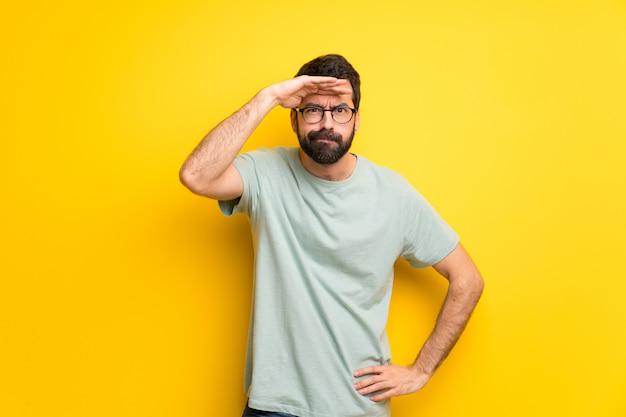 L'uomo con la barba e la camicia verde guardando lontano con la mano per guardare qualcosa