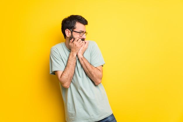 L'uomo con la barba e la maglietta verde è un po 'nervoso e spaventato a mettere le mani in bocca