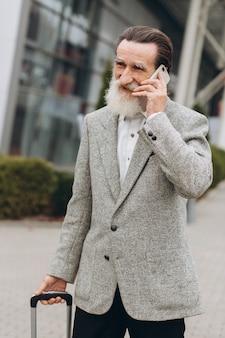 L'uomo con la barba grigia senior con la valigia e lo smartphone di trasporto sta camminando lungo l'edificio dell'aeroporto. sta guardando da parte pensieroso. copia spazio sul lato destro