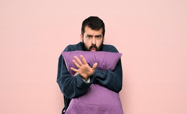 L'uomo con la barba in pigiama nervoso allungando le mani in avanti su sfondo rosa isolato