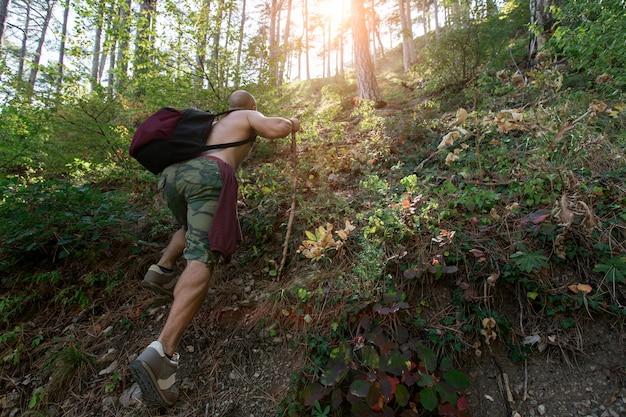 L'uomo con lo zaino si arrampica fino alla collina