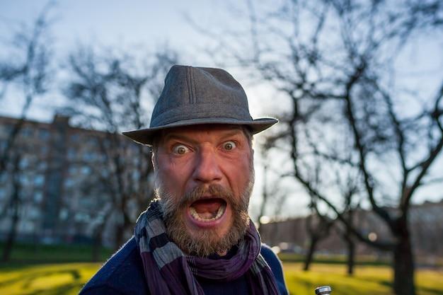 L'uomo con un cappello urla di sorpresa