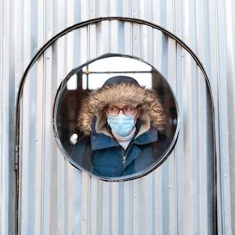 L'uomo con un cappuccio guarda fuori dalla finestra rotonda, indossando una maschera protettiva per il viso