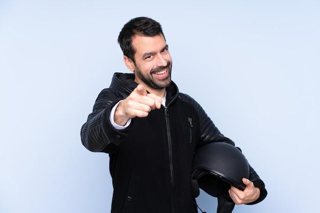 L'uomo con un casco da motociclista sopra il muro isolato punta il dito contro di te con un'espressione fiduciosa