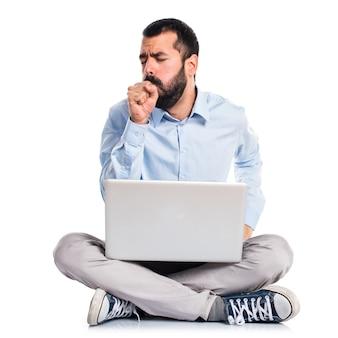 L'uomo con un computer portatile tende molto