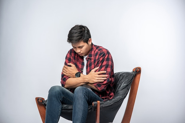 L'uomo con una camicia a righe siede malato, si siede su una sedia e incrocia le braccia.