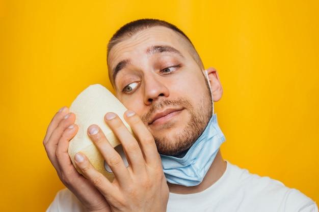 L'uomo con una camicia blu avvolse il viso nella carta igienica, cercando di proteggersi dal coronavirus. in studio su uno sfondo giallo. proteggere la salute dai virus.