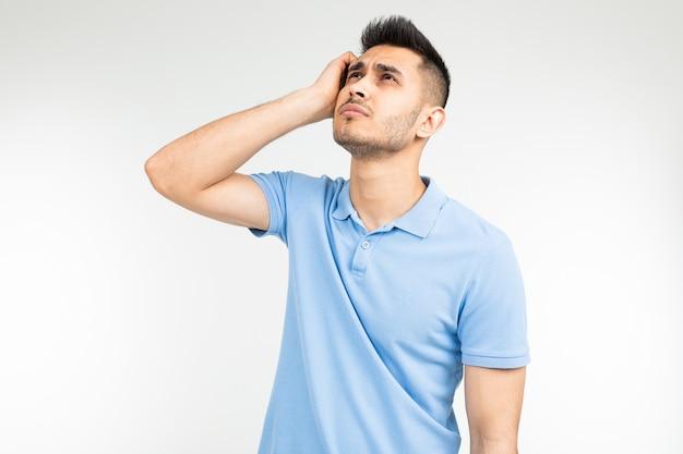 L'uomo con una camicia blu che pensa a un'idea su un bianco ha isolato il fondo