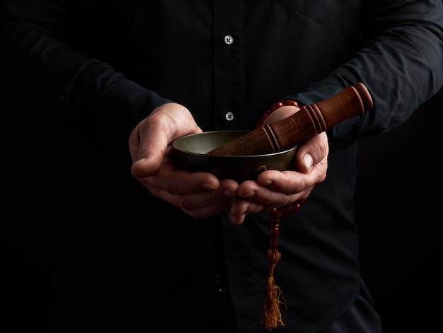 L'uomo con una camicia nera tiene una ciotola tibetana in ottone e un bastone di legno, un rituale di meditazione