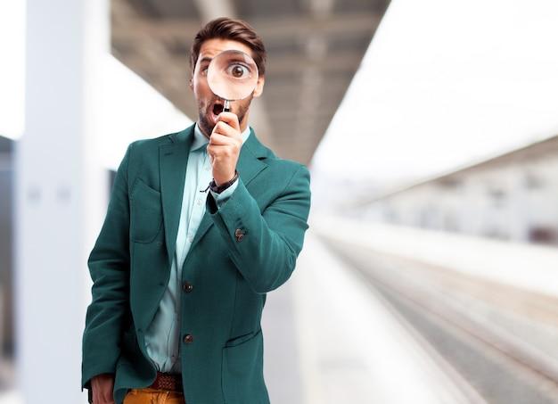 L'uomo con una lente di ingrandimento nella stazione ferroviaria