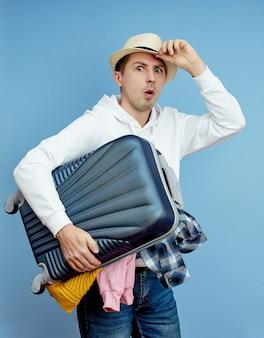L'uomo con una valigia si affretta verso l'aereo, le cose cadono dal bagaglio