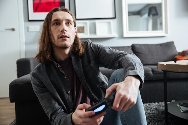 L'uomo concentrato che si siede a casa all'interno gioca con la leva di comando