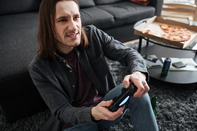 L'uomo concentrato che si siede a casa all'interno gioca