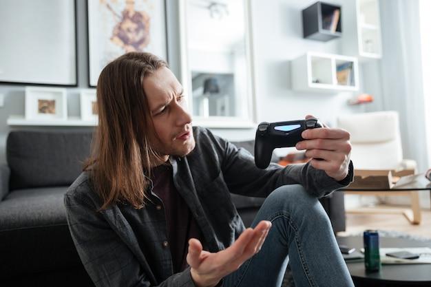 L'uomo confuso che si siede a casa all'interno gioca con il joystick.