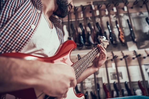 L'uomo controlla la chitarra elettrica in negozio.