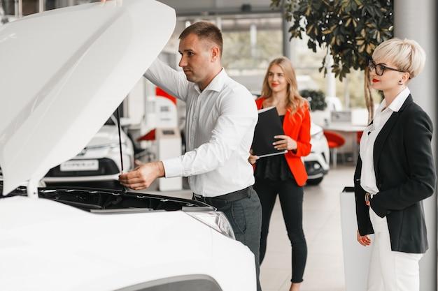L'uomo controlla la macchina aprendo un cofano. la donna sta vicino a lui e guarda felicemente.