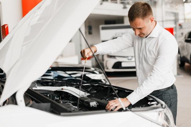 L'uomo controlla la presenza di olio nel primo piano della macchina