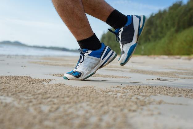 L'uomo corre sulla spiaggia, primo piano su scarpe