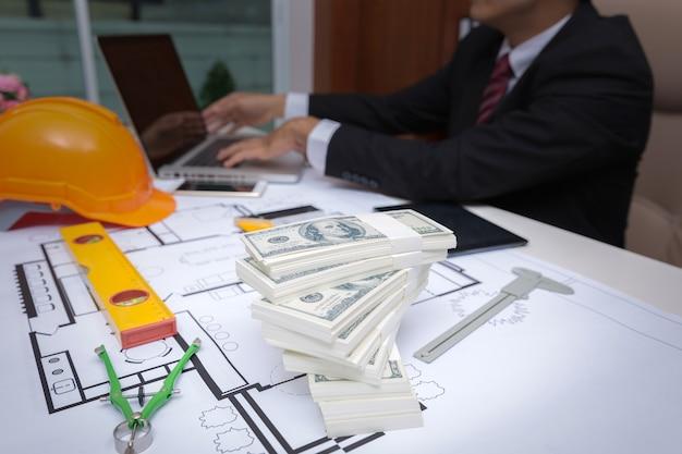 L'uomo corrotto accetta la bustarella delle banconote dal progetto di costruzione della costruzione.