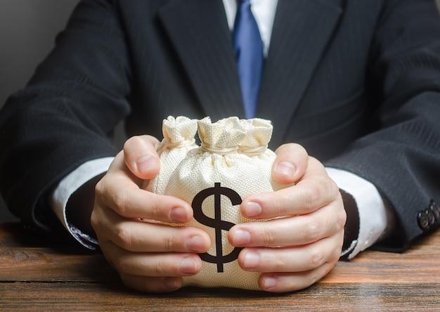 L'uomo d'affari abbraccia i sacchetti dei soldi del dollaro us.