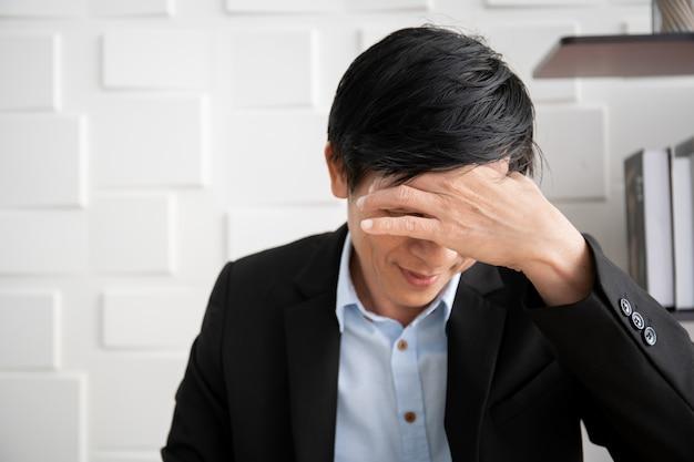 L'uomo d'affari asiatico anziano ha il problema della sindrome dell'ufficio dal duro lavoro. assistenza sanitaria e concetto di conciliazione vita-lavoro nei lavoratori.