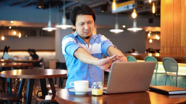 L'uomo d'affari asiatico in vestito casuale che lavora soffrendo dai dolori e dai dolori