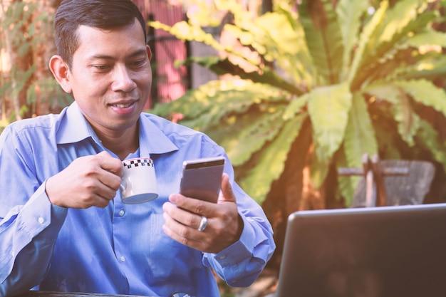 L'uomo d'affari asiatico sorride mentre riceve un messaggio di testo dallo smartphone