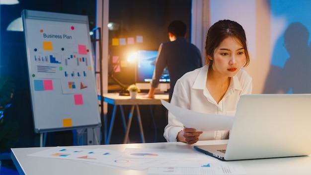 L'uomo d'affari asiatico spegne il computer e saluta il suo collega che lavora ancora quando smette di lavorare dopo aver finito di fare gli straordinari nella notte di un piccolo ufficio domestico moderno. concetto di collaborazione di un collega.