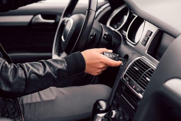 L'uomo d'affari avvia la sua automobile moderna alla moda con la chiave