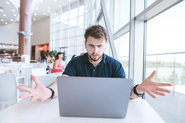 L'uomo d'affari barbuto sorpreso si siede in un caffè, guarda lo schermo del computer portatile e si rompe le mani